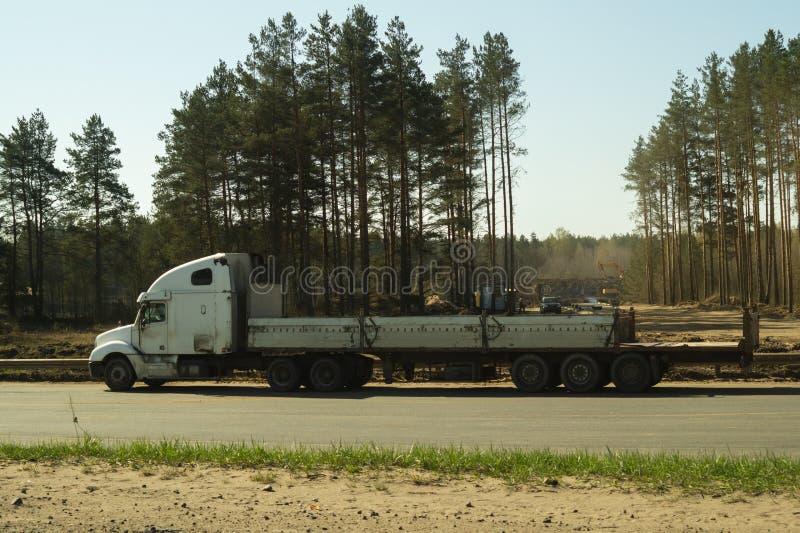 Grande camion sul bordo della strada vicino al camion bianco della foresta su una strada immagine stock
