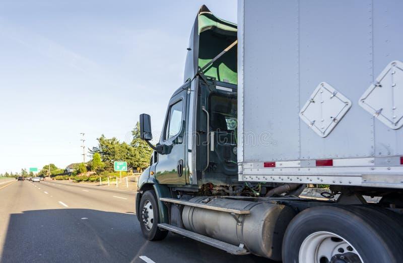 Grande camion verde scuro dei semi della carrozza di giorno dell'impianto di perforazione con il diruttore del tetto che trasport fotografie stock
