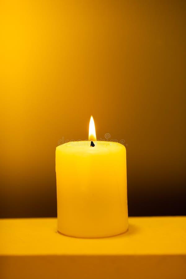 Grande candela accesa su un fondo giallo caldo fotografie stock