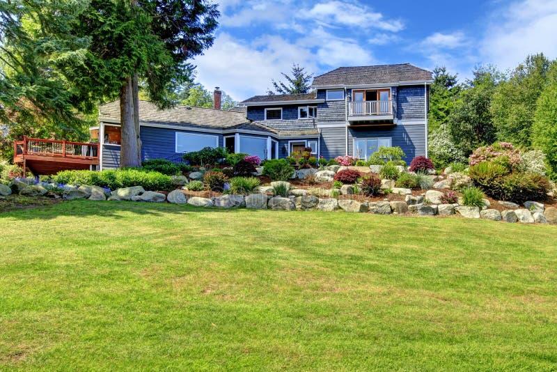 Grande casa blu sulla collina con sbarco verde. fotografia stock libera da diritti