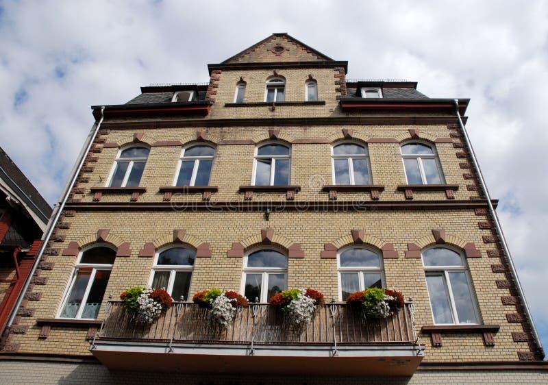 Grande casa con il balcone fiorito e grandi finestre bianche in Bacharach lungo la valle del Reno in Germania fotografia stock