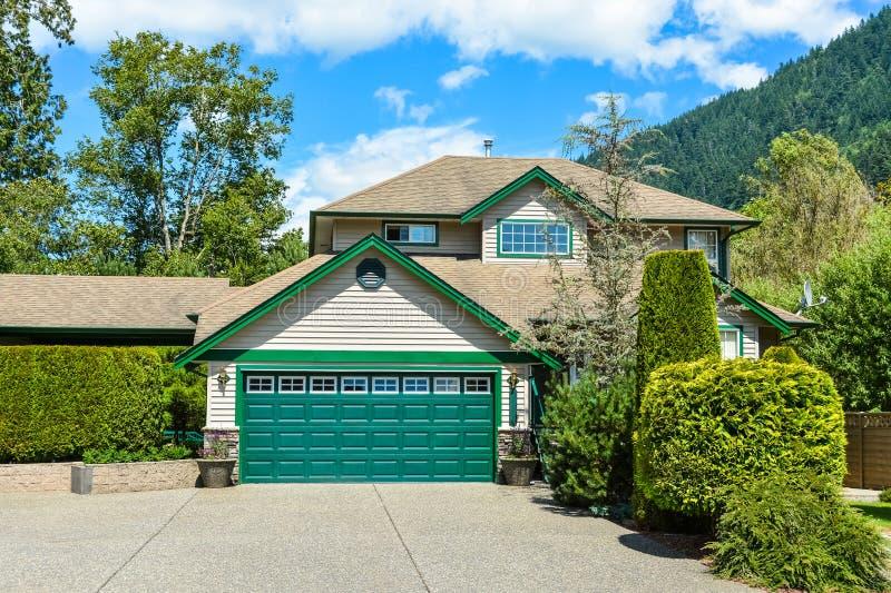 Grande casa della famiglia con l'ampia strada privata concreta e l'ampia porta verde del garage fotografie stock