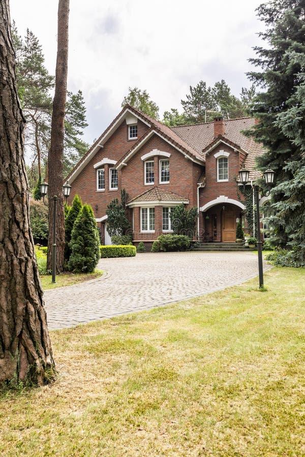 Grande casa destacada exterior com paredes de tijolo e o behi vermelho do telhado imagem de stock
