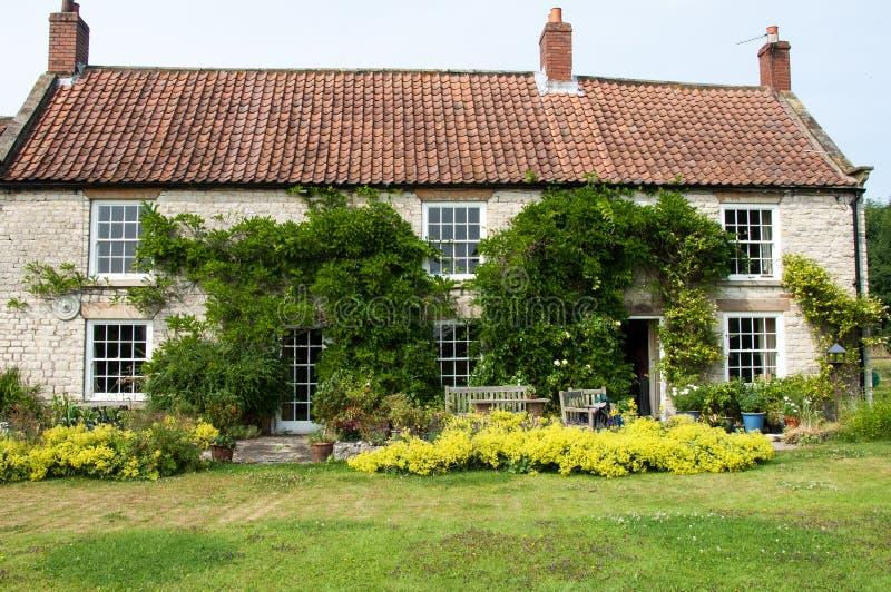 Grande casa di campagna e giardino convenzionale fotografia stock libera da diritti