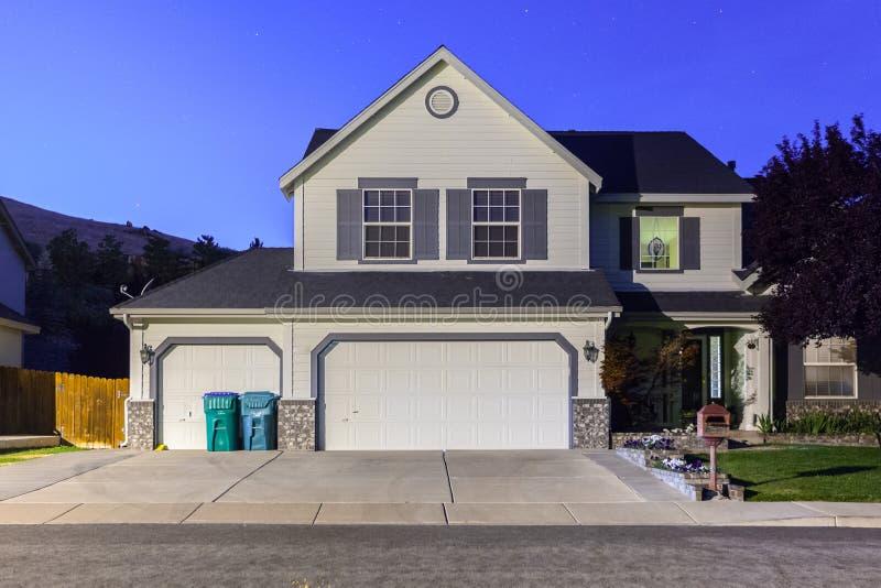 Grande casa di lusso con le porte triple del garage al crepuscolo, notte in subu immagini stock libere da diritti