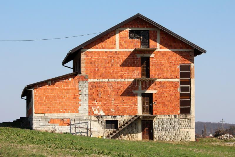 Grande casa suburbana inacabado da fam?lia do tijolo vermelho no lado do monte pequeno cercado com grama sem cortes fotografia de stock royalty free