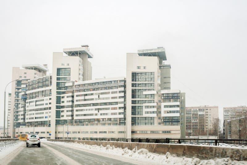 Grande casa urbana com construção complexa, estrada perto dele e céu branco do inverno com espaço da cópia foto de stock
