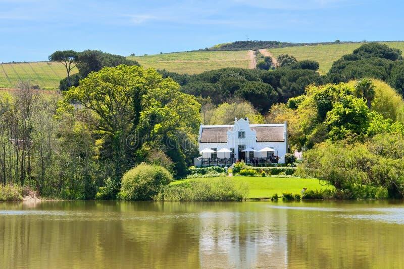Grande casa vicino al lago ed alle colline fotografia stock libera da diritti