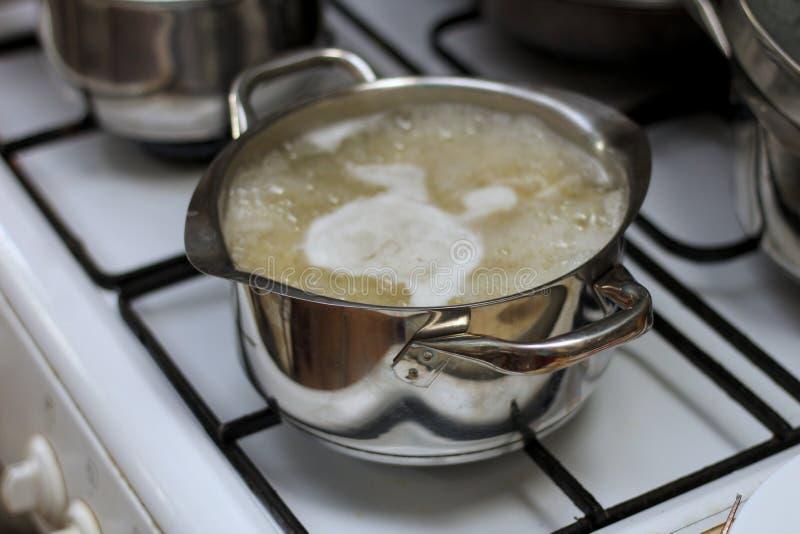 grande casserole brillante en métal sur le fourneau avec le sirop de sucre bouillant dans lui images stock