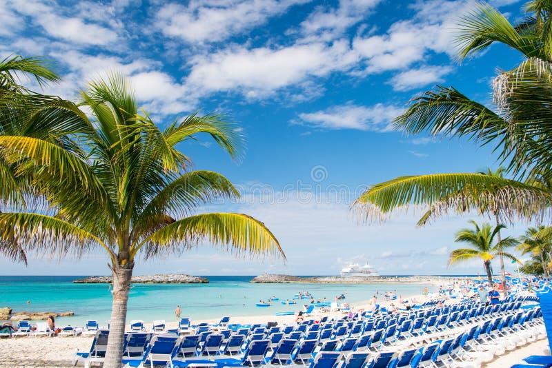 Grande cay do estribo, Bahamas - 8 de janeiro de 2016: praia do mar, pessoa, cadeiras, palmeiras verdes no dia ensolarado Férias  imagem de stock