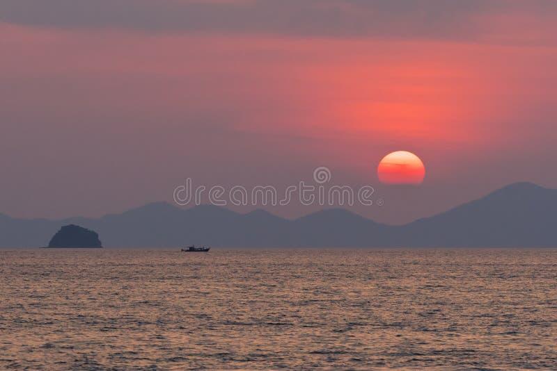 Grande cerchio rosso del sole negli insiemi di una foschia dietro la siluetta delle montagne e delle nuvole sul fotografia stock