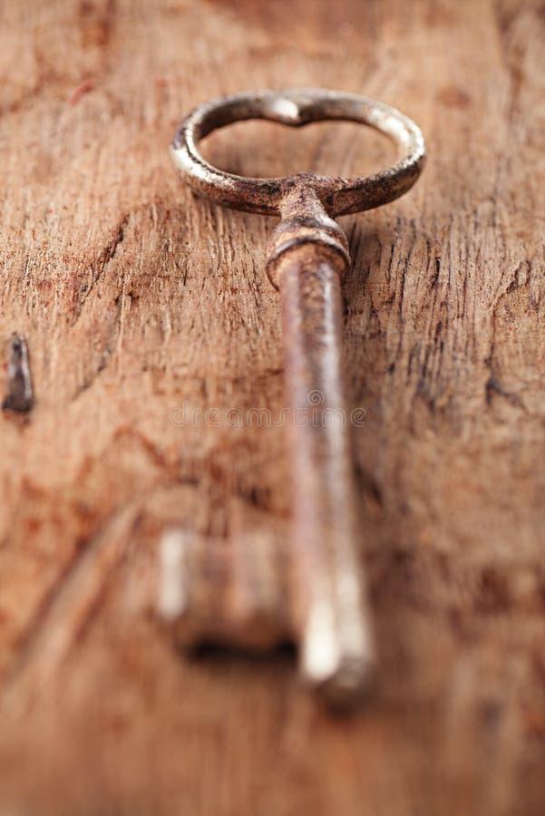 Grande chave oxidada do metal do vintage no fundo de madeira velho fotografia de stock royalty free
