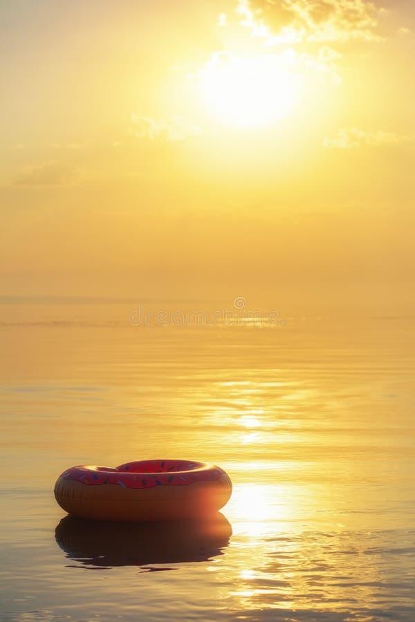 Grande ciambella gonfiabile su acqua nel tempo di alba I pantaloni a vita bassa hanno spruzzato il galleggiante della ciambella i immagine stock