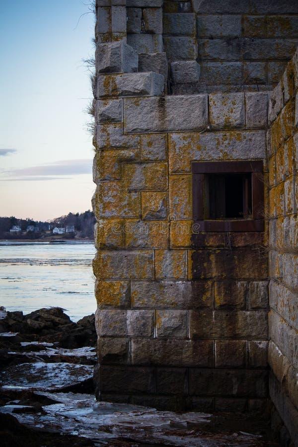 Grande construção abandonada pedra-feita na costa do mar antes do crepúsculo com molde fotografia de stock royalty free