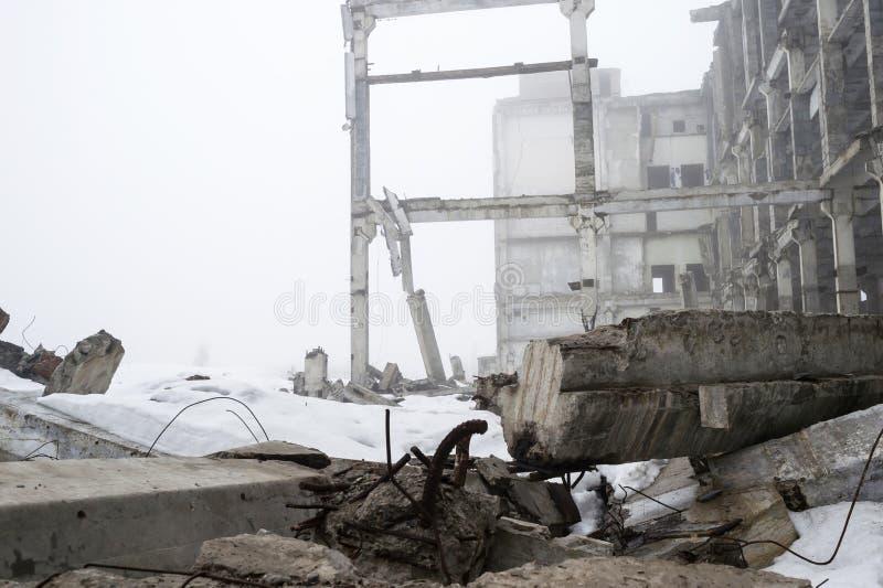 Grande costruzione concreta distrutta in una foschia nebbiosa con il resti di neve Fondo fotografia stock libera da diritti