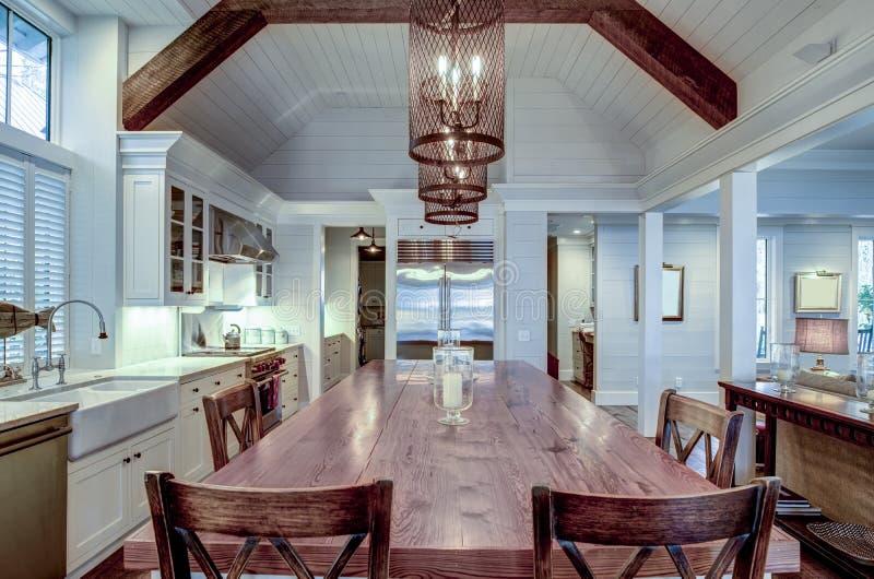 Grande cozinha de luxo com mesa de madeira e aparelhos sofisticados imagem de stock royalty free