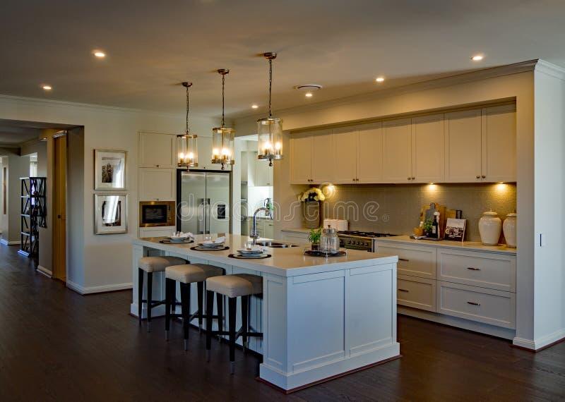Grande cozinha luxuoso com iluminação ambiental e o assoalho de madeira fotografia de stock royalty free