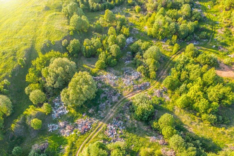 Grande décharge des déchets, des déchets de ménage, des plastiques et d'autres choses parmi la forêt verte le long des prés et de image stock