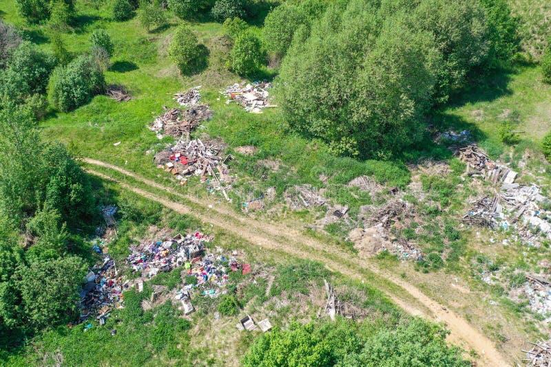 Grande décharge des déchets, des déchets de ménage, des plastiques et d'autres choses parmi la forêt verte le long des prés et de photographie stock libre de droits