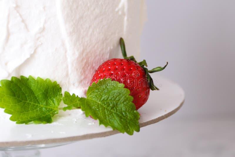 Grande dolce delizioso bianco con crema e decorato con le fragole e la menta su un supporto trasparente su un fondo grigio fotografia stock