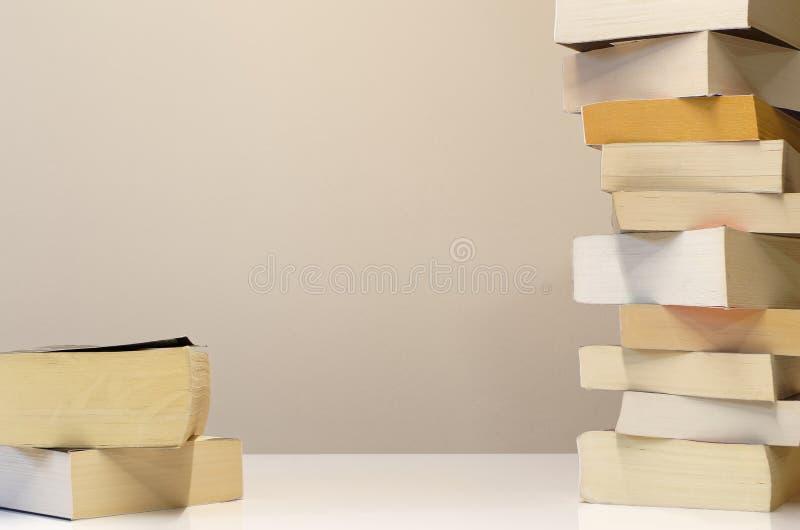 Grande e piccolo mucchio dei libri sulla tavola bianca fotografia stock libera da diritti