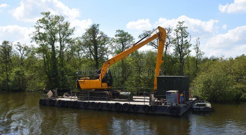 Grande escavatore meccanico sul pontone di galleggiamento immagini stock libere da diritti