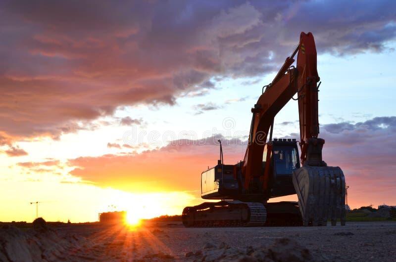 Grande escavatore seguito su un cantiere contro lo sfondo del tramonto impressionante fotografia stock libera da diritti