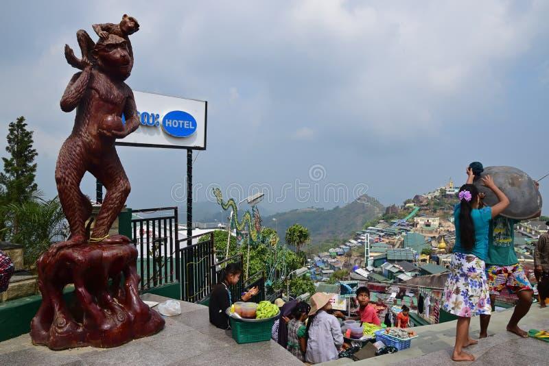 Grande estátua marrom do macaco na esquerda com a comunidade do alojamento no direito atrás da rocha dourada (pagode de Kyaiktiyo foto de stock royalty free