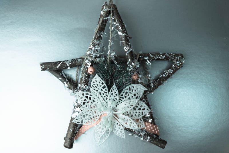 Grande estrela de madeira bonita decorativa do Natal, ramos feitos a si próprio e varas de um abeto da grinalda do advento no ano foto de stock royalty free