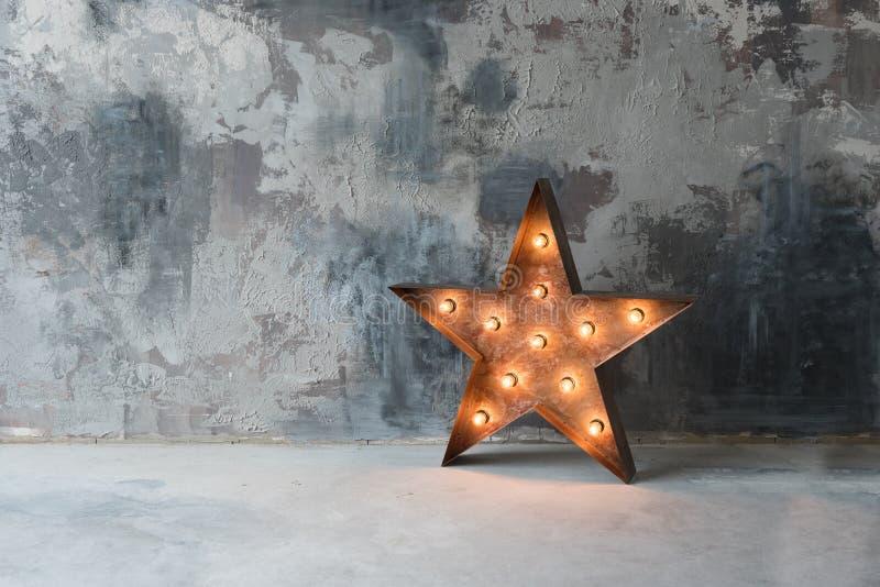 Grande estrela retro decorativa com lotes de luzes ardentes no fundo do concreto do grunge Decoração bonita, projeto moderno fotografia de stock royalty free