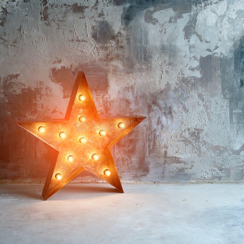 Grande estrela retro decorativa com lotes de luzes ardentes no fundo do concreto do grunge Decoração bonita, projeto moderno imagens de stock