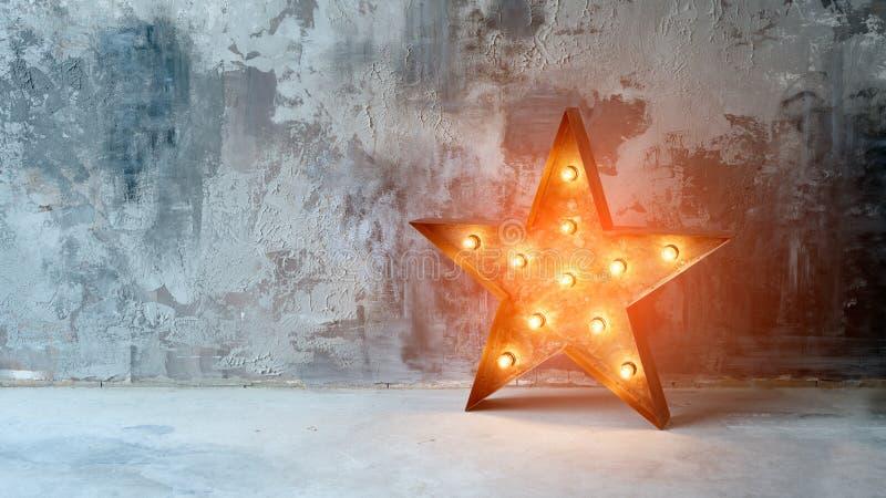 Grande estrela retro decorativa com lotes de luzes ardentes no fundo do concreto do grunge Decoração bonita, projeto moderno foto de stock