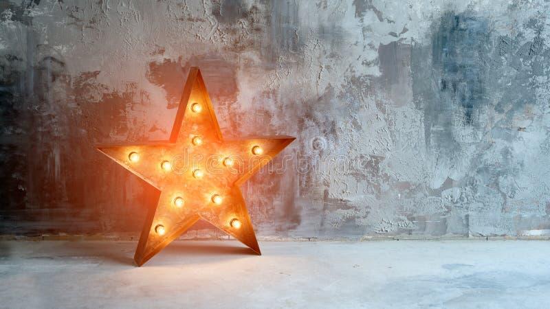 Grande estrela retro decorativa com lotes de luzes ardentes no fundo do concreto do grunge Decoração bonita, projeto moderno imagem de stock royalty free
