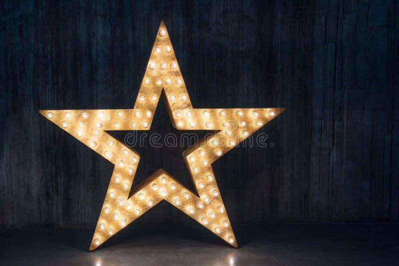 Grande estrela retro decorativa com lotes de luzes ardentes no fundo do concreto do grunge Decoração bonita, elemento do projeto  foto de stock royalty free