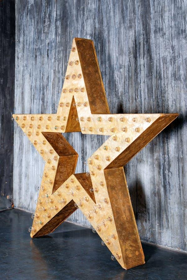 Grande estrela retro decorativa com lotes de luzes ardentes no fundo do concreto do grunge Decoração bonita, elemento do projeto  fotografia de stock royalty free