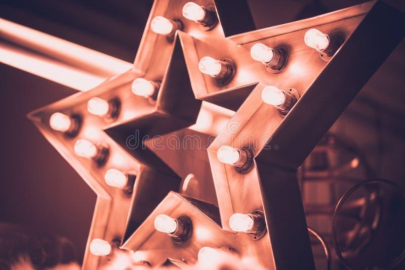 Grande estrela retro decorativa com lotes de luzes ardentes no fundo do concreto do grunge Decoração bonita, elemento do projeto  fotografia de stock