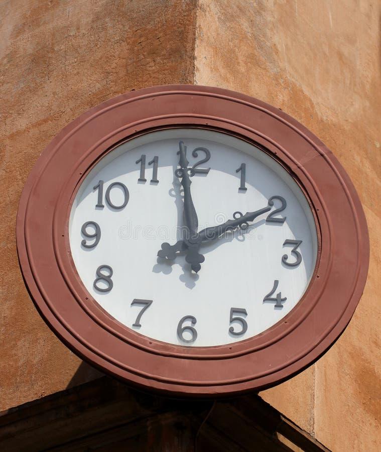Grande et circulaire horloge murale qui marque les deux heures image stock