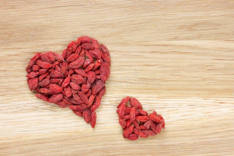 Grande et petite forme de coeur faite de baies de goji images libres de droits
