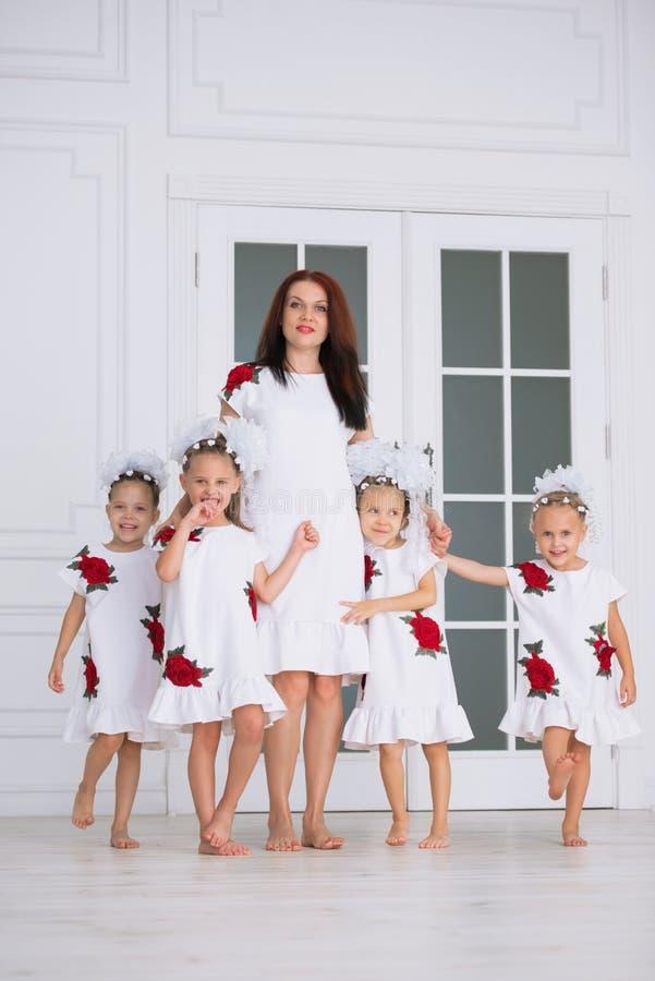 Grande família feliz da mãe com as quatro filhas em vestidos brancos bordados oposto à porta no interior imagem de stock