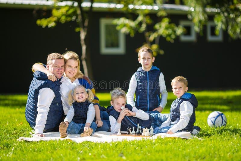 Grande famiglia che si rilassa in natura verde Il ritratto felice su all'aperto, il gruppo sei persone della famiglia si siede su immagini stock libere da diritti