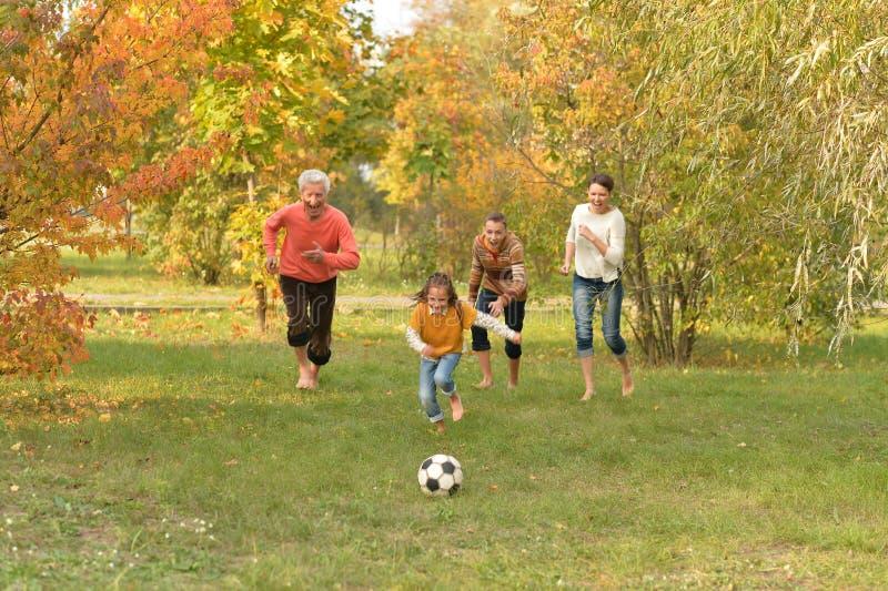 Grande famiglia felice che gioca a calcio nel parco di autunno fotografie stock