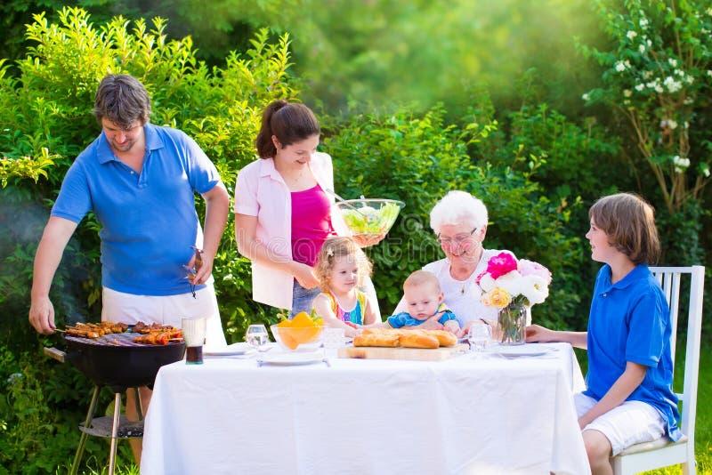 Grande famiglia felice che gode della griglia del bbq nel giardino fotografie stock