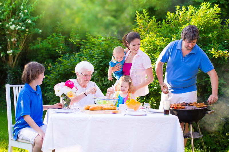 Grande famiglia felice che gode della griglia del bbq nel giardino fotografia stock libera da diritti
