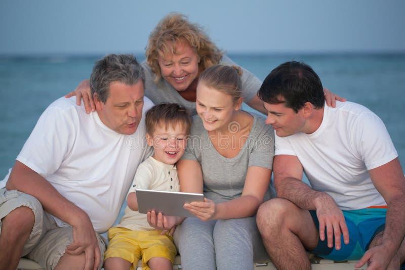 Grande famiglia felice con il PC della compressa sulla spiaggia fotografia stock libera da diritti