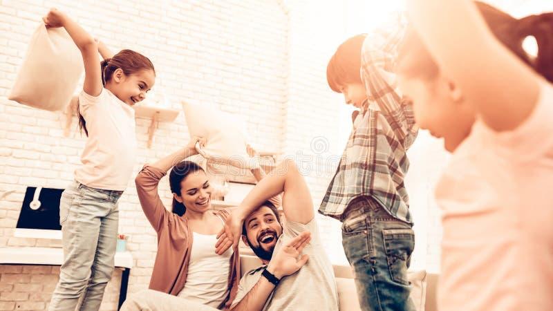 Grande famiglia sveglia felice che ha lotta di cuscino immagine stock