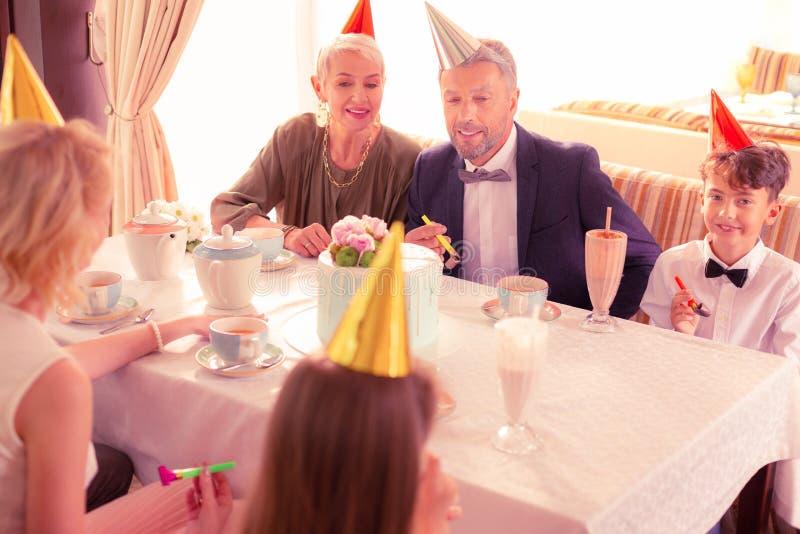 Grande famille célébrant le garçon aux cheveux foncés beau d'anniversaire images libres de droits