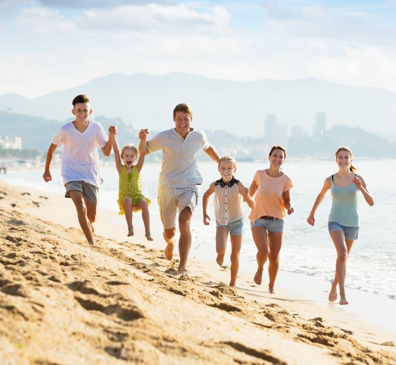 Grande famille courant sur la plage photos stock