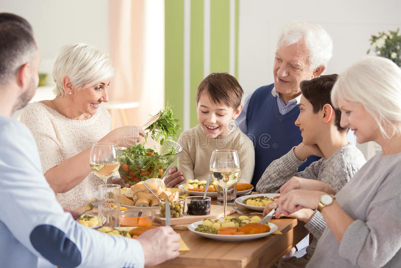Grande famille heureuse mangeant le dîner images stock