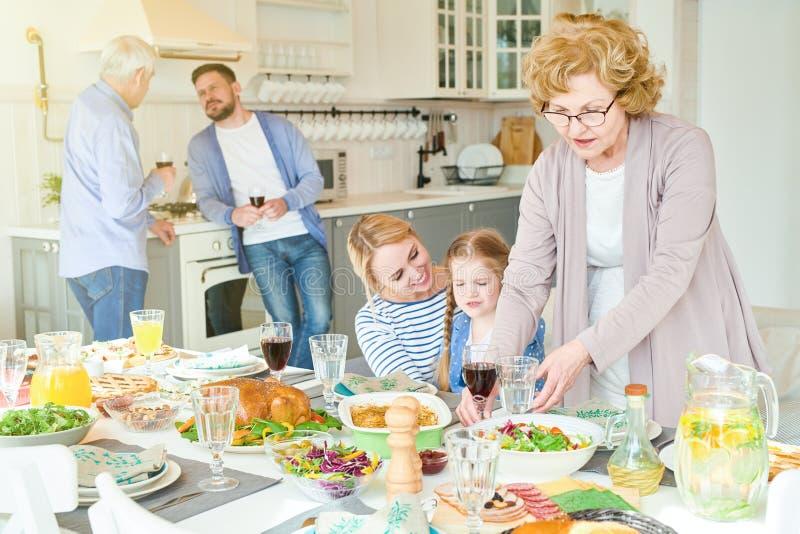 Grande famille heureuse préparant le Tableau de dîner pour la partie photos libres de droits