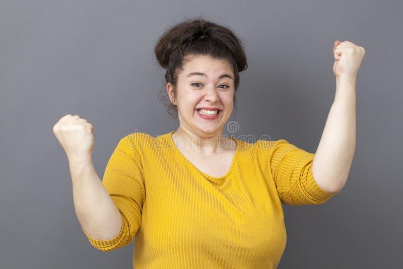 Grande femme 20s joyeuse exprimant la victoire d'amusement photo stock